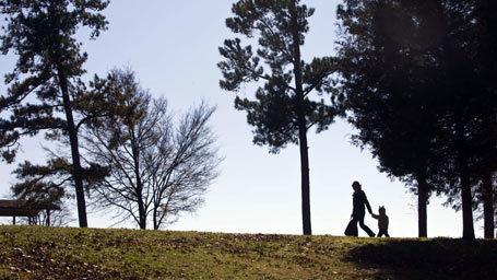 Adult and child walking on grass